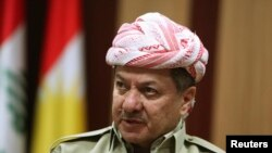 "FILE - Iraqi Kurdistan President Masoud Barzani says the killers of the Kurdish fighters ""will see how the hand of the heroic peshmerga will reach them."""