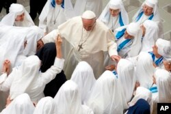 Pope Francis is greeted by a group of nuns during his weekly general audience in the Pope Paul VI hall at the Vatican, Wednesday, Aug. 22, 2018.