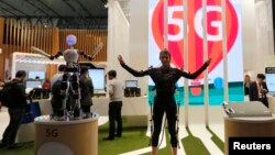 An SK telecom exhibitor directs the robot's movements using 5G on the last day at the Mobile World Congress in Barcelona.