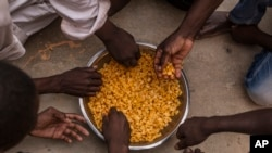 Migrants share a bowl of pasta during their lunch at the courtyard of a detention center for migrants, in the village of Karareem, around 50 kilometers from Misrata, Libya, Sept. 25, 2016. Libya is an important transit and destination country for migrants who arrive seeking employment or a path to Europe.