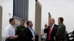 President Donald Trump reviews border wall models, March 13, 2018, in San Diego. (AP Photo/Evan Vucci)