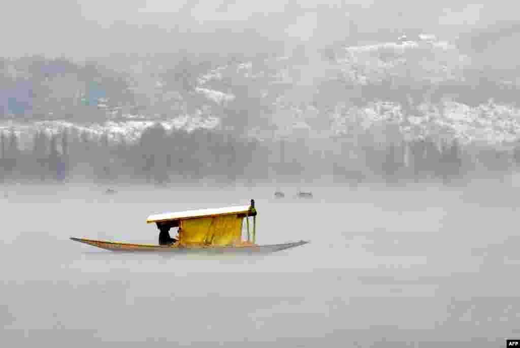 Kashmiri boatmen paddle a shikara across Dal Lake amid dense fog following rainfall in Srinagar, India.
