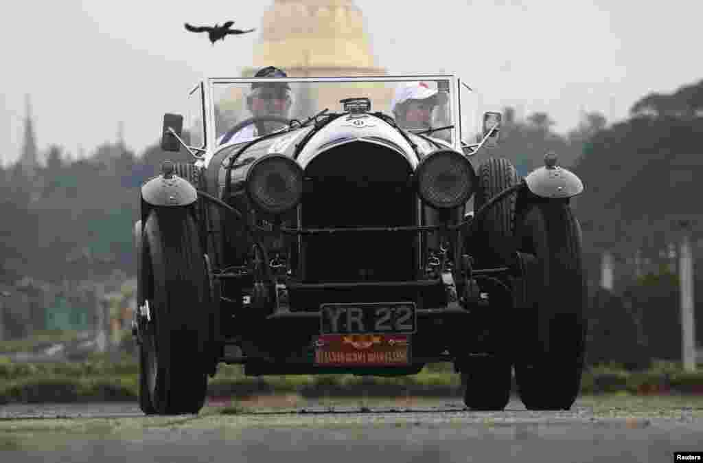 """A 1928 Bentley classic car stops in front of Shwedagon pagoda during the start of """"The Burma Road Classic"""" motoring rally in Rangoon, Burma."""