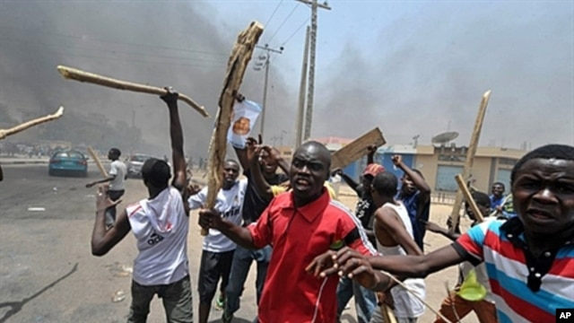 People holding wooden and metal sticks demonstrate in Nigeria's northern city of Kano where running battles broke out between protesters and soldiers on April 18, 2011 as President Goodluck Jonathan headed for an election win