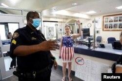 Un padre y una miembro de los 'Patriotas de la comunidad' se enfrentan a un agente de policía mientras protestan contra el uso de mascarillas en las escuelas, en Largo, Florida, el 9 de agosto de 2021.