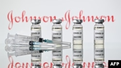 (FILES) This file illustration photo taken on November 17, 2020 shows vials with Covid-19 Vaccine stickers attached and syringes with the logo of US pharmaceutical company Johnson & Johnson. - Pharmaceuticals giant Johnson & Johnson on February 4,…