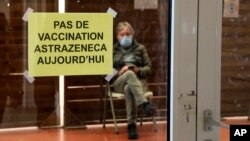 """A man waits in a vaccination center where a sign reads """"No AstraZeneca vaccinations today"""" in Saint-Jean-de-Luz, southwestern France, Tuesday, March 16, 2021."""