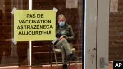 """A man waits in a vaccination center where a sign reads """"No AstraZeneca vaccinations today"""" in Saint-Jean-de-Luz, southwestern France, Tuesday, March 16, 2021. With coronavirus cases rising in many places, governments faced the grimmest of dilemmas…"""