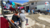 Inmigrantes aguardan sentados en el patio del refugio El Buen Samaritano, en Ciudad Juárez, México, su hogar durante la larga espera, en ocasiones, ya de años.