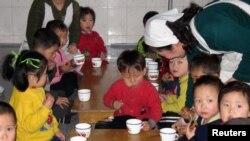북한 룡천의 한 고아원에서 세계식량계획(WFP)이 제공한 옥수수-콩 혼합 간식을 먹는 어린이들.
