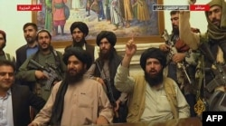 An image grab taken from Qatar-based Al-Jazeera television on August 16, 2021, shows members of the Taliban taking control of the presidential palace in Kabul.
