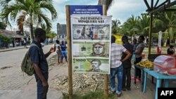 Un migrante varado mira un cartel sobre inversiones en Necoclí, Colombia, el 29 de julio de 2021.