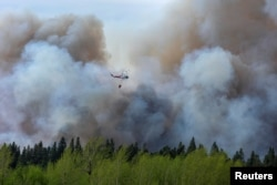 FILE - Water droppers battle an out of control forest fire after the city of Prince Albert declared a state of emergency over a fast-moving wildfire, prompting some residents to evacuate, in Prince Albert, Saskatchewan, Canada, May 18, 2021.