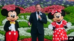 Joe Schott, center, president and general manager of Shanghai Disney Resort, speaks, along with Mickey and Minnie Mouse, during its reopening ceremony after the coronavirus closure in Shanghai, China, Monday, May 11, 2020. Visits will be limited…