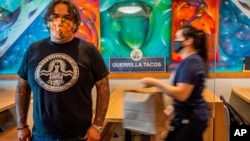 Guerrilla Tacos chef-owner Wes Avila poses for a picture, as an employee in a face mask delivers to go orders at his critically acclaimed restaurant in Los Angeles, Friday, July 3, 2020. California restaurants are paying a heavy price during the…