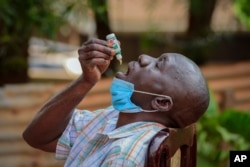 FILE - A man with a cough but who had not been tested for the coronavirus uses COVIDEX, a locally-made herbal medicine approved by the government for use as a supportive treatment for viral infections, in Kampala, Uganda, July 6, 2021.