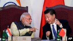 ນາຍົກລັດຖະມົນຕີ ອິນເດຍ ທ່ານ ນາເຣັນດຣາ ໂມດີ, ຊ້າຍ, ລົມກັບປະທານປະເທດ ຈີນ ທ່ານ ສີ ຈິ່ນຜິງ ໃນພິທີເຊັນສັນຍາ ໂດຍບັນດາລັດຖະມົນຕີຕ່າງປະເທດ ໃນລະຫວ່າງກອງປະຊຸມສຸດຍອດ BRICS ໃນເມືອງ ກົວ, ປະເທດ ອິນເດຍ. 16 ຕຸລາ, 2016.
