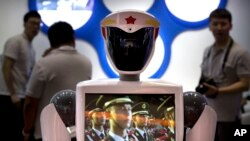 FILE - A video screen plays footage of Chinese People's Liberation Army (PLA) soldiers on a robot from a Chinese robot maker at the World Robot Conference in Beijing, China, Aug. 15, 2018.