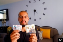 """Jesus Lopez, who was deported from the U.S. last year, holds up his Illinois driver's license and a family snapshot, at his home in Zapopan, Jalisco state, Mexico, May 13, 2021. """"I belong there,"""" the DACA recipient says of Chicago."""