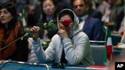 Una mujer iraní estadounidense que apoya al Consejo Nacional de Resistencia de Irán lleva una rosa en el Centro de Convenciones de Los Ángeles, el sábado 11 de enero de 2020.