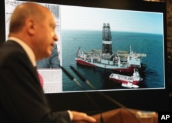 Turkey's President Recep Tayyip Erdogan speaks with the Turkish drilling ship Fatih, in background, in Istanbul, Aug. 21, 2020.