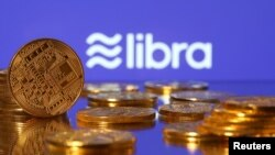 FILE - Representations of virtual currency are displayed in front of the Libra logo in this illustration picture.