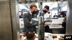 French President Emmanuel Macron (C) talks with students, on June 8, 2021 in the kitchen of the Hospitality school in Tain-l'Hermitage, during a visit in the south-eastern France department of Drome, the second stage of a nationwide tour ahead of…