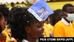 Une femme portant un tract de campagne électorale du Président sortant Patrice Talon et de sa colistière Mariam Talata participe à un meeting de campagne à Abomey-Calavi, le 9 avril 2021.