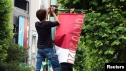 Workers attach the Tokyo 2020 Olympic Games banner on a lamp post in Tokyo, Japan, June 16, 2021.