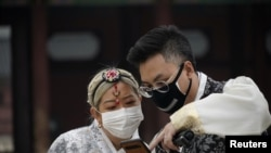 FILE - A couple wearing masks to prevent contacting the coronavirus looks at a mobile phone at Gyeongbok Palace in central Seoul, South Korea, March 1, 2020.