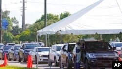 FILE - Cars line up at Miami Dade College North Campus' COVID-19 testing site, July 29, 2021, in Miami. Hospital admissions of coronavirus patients continue to soar in Florida.