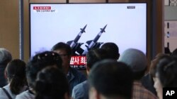 People watch a TV broadcast showing file footage of North Korean missiles, during a news program at the Seoul Railway Station, in Seoul, South Korea, May 9, 2019. North Korea reportedly launched two projectiles off its east coast early Thursday.