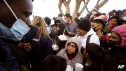 Asylum-seekers receive food as they wait for news of policy changes at the border, in Tijuana, Mexico, Feb. 19, 2021.