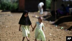 FILE - Young girls hold hands as they walk down a road in Marawi City, southern Philippines, June 15, 2018. A coronavirus lockdown in the region has brought a welcome reprieve in fighting between government forces and Muslim rebels seeking independence.