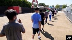 Niños migrantes caminan juntos después de un partido de fútbol en un refugio de emergencia para niños migrantes el viernes 2 de julio de 2021 en Pomona, California.