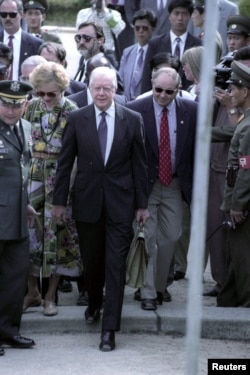 FILE - Former U.S. President Jimmy Carter crosses the military demarcation line in Panmunjom from North to South Korea, June 18, 1994.