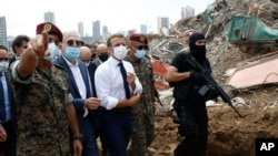 French President Emmanuel Macron, center, visits the devastated site of the explosion at the port of Beirut, Lebanon, Aug. 6, 2020.