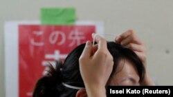 Un agent de santé enlève un masque de protection dans le service de soins intensifs pour les patients atteints de COVID-19 à l'hôpital universitaire St. Marianna à Kawasaki, au Japon, le 4 mai 2020.