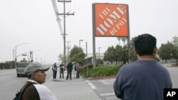 FILE - Only a few day laborers seek work near a skilled labor site at a Home Depot in Glendale, Calif.