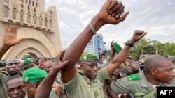 Colonel Malick Diaw, center, vice-president of the CNSP (National Committee for the Salvation of the People), gestures to supporters as he arrives escorted by Malian soldiers at the Independence Square in Bamako, Aug. 21, 2020.