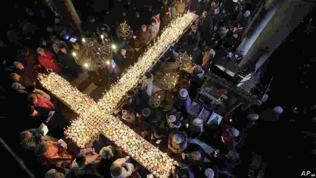 불가리아 수도 소피아에서 100km 떨어진 블라고에브그라드의 교회에서 '꿀의 축성'을 위한 미사가 열린 가운데 신자들이 꿀단지에 담긴 촛불 주위로 모여있다.