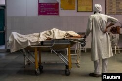 FILE - A man stands next to the body of his wife, who died due to breathing difficulties, inside an emergency ward of a government-run hospital, amidst the coronavirus pandemic, in Bijnor, Uttar Pradesh, India, May 11, 2021.
