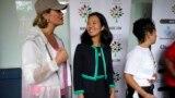 Dua kandidat walikota Boston Annissa Essaibi George (kiri) dan Michelle Wu (tengah), tampak berbincang sebelum parade Roxbury Unity berlangsung di kota Boston pada 18 Juli 2021. (Foto: AP)