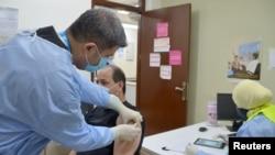 FILE - A Palestinian man receives the COVID-19 vaccine inside a medical center at Baqaa refugee camp, near Amman, Jordan April, 12, 2021.