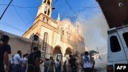 "Warga berkumpul di sekitar lokasi ledakan bom mobil di luar Gereja Ortodoks ""Virgin Lady"" di kawasan al-Wasti, kota Qamishli di Suriah timur laut, 11 Juli 2019."