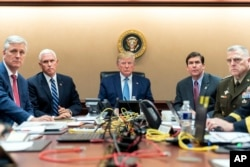 In this image released by the White House, President Donald Trump is joined by others to watch U.S. Spacial Operations forces close ion on al-Baghdadi.