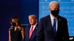 អ្នកស្រី Melania Trump (ឆ្វេង) និងលោកប្រធានាធិបតី Donald Trump (កណ្ដាល) ឈរនៅលើឆាក ខណៈលោក Joe Biden ដើរចេញ ក្រោយពីជជែកដេញដោលលើកទីពីររួច ថ្ងៃទី២២ ខែតុលា ឆ្នាំ២០២០។
