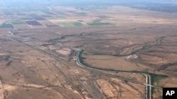 FILE - In this Oct. 8, 2019 photo, the Central Arizona Project canal runs through rural desert near Phoenix, Arizona.