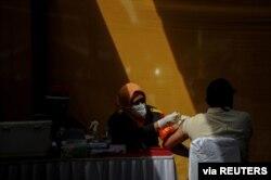 Seorang buruh divaksinasi COVID-19 di sebuah pabrik di Sumedang, Jawa Barat, 5 Agustus 2021. (REUTERS)