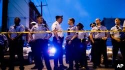 Para petugas kepolisian berkumpul dekat sebuah rumah saat menyelidiki penembakan di Philadelphia, 14 Agustus 2019. (AP Photo/Matt Rourke)